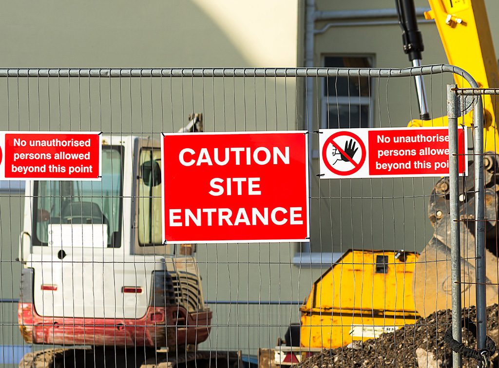 An image of a worksite guarded by a gate, with a red sign saying 'CAUTION SITE ENTRANCE' to display site security