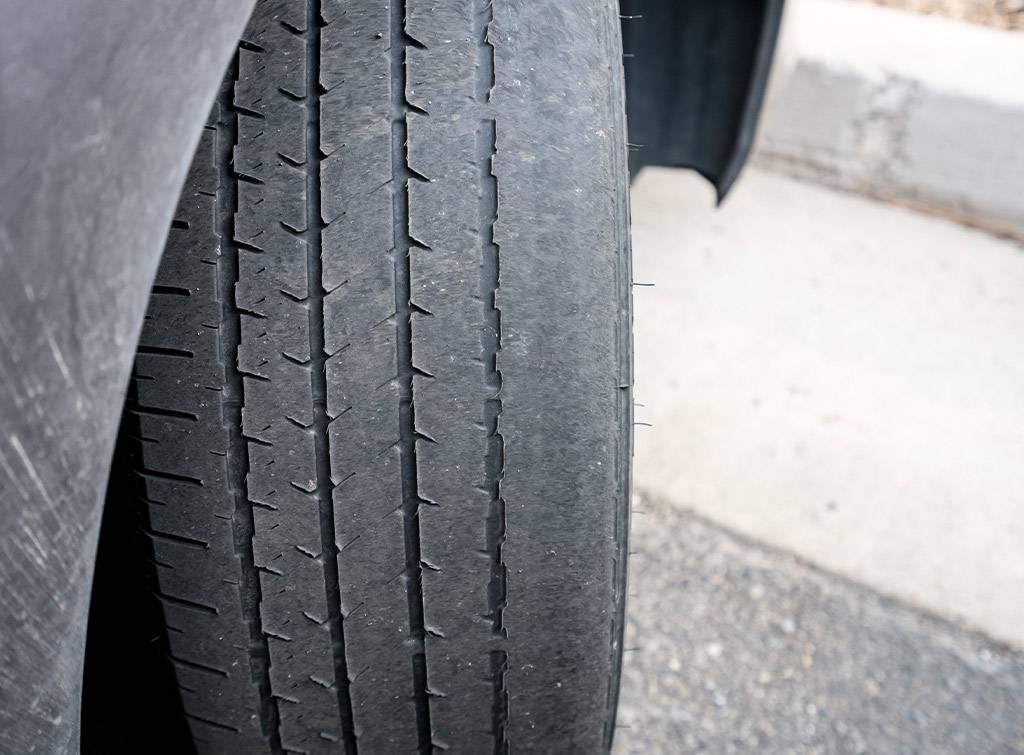 Front wheel tires or tyres on car badly worn